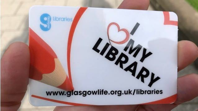 Image of hand holding library card