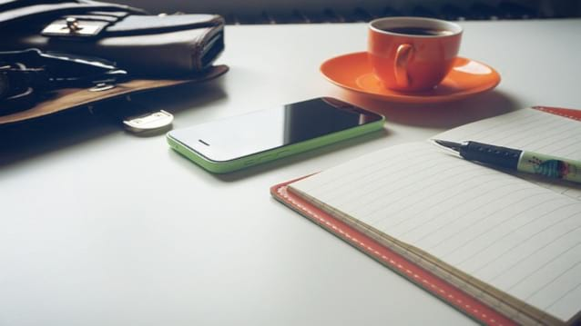 Image of a pen and notebook, coffee cup and mobile phone