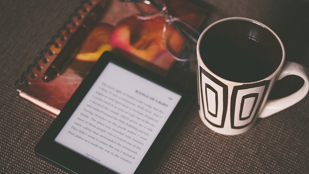 e-book reader, notebook, pen, spectacles and mug of coffee on table