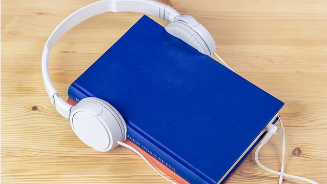 Headphones plugged into a book sitting on a table